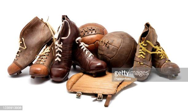 Vintage eather football equipment including three pairs of football boots with leather studs, a pair of shin pads with rubberised backing and two...