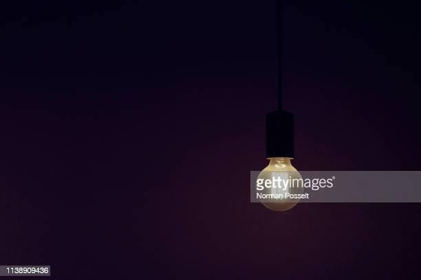vintage electric light bulb illuminated against black background - inspiration stock-fotos und bilder