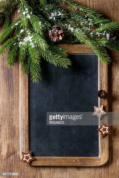 Vintage empty chalkboard with fir Christmas tree and wood modern decor stars over wooden background Top view with space for text