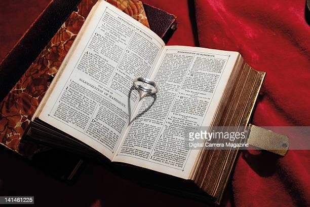 A vintage etiquette book open at a section describing matrimonial vows with a wedding ring between the pages casting a heartshaped shadow taken on...