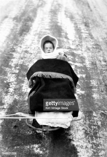 Vintage family photo of baby on a sled, ca. 1947.