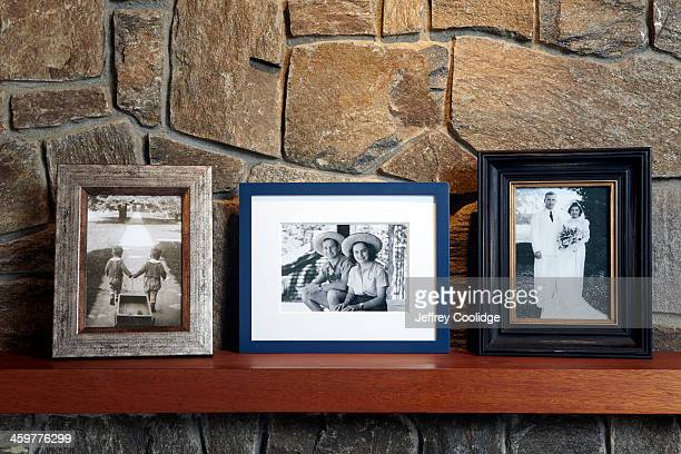 vintage family photos on mantle - photography photos stock photos and pictures