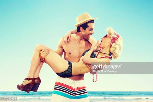 Vintage fashion couple being playful by the beach