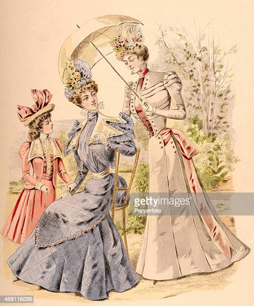 A vintage fashion illustration featuring two stylish ladies and a young girl wearing day dresses and ornate hats in a parkland setting circa 1898