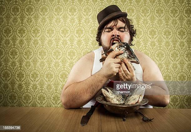 vintage gros homme manger la soupe de poisson de la tête sur une table en bois