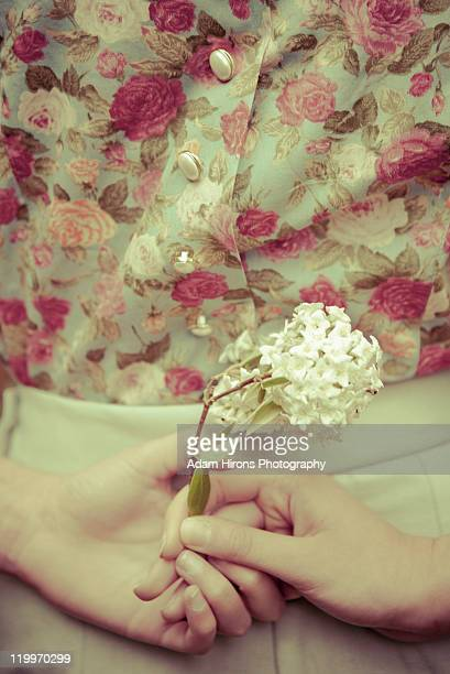 vintage female holding flower in hands around back - mid section stock photos and pictures