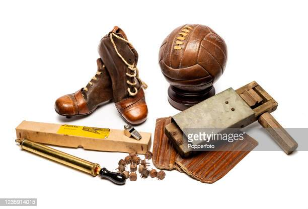 Vintage football paraphernalia including a pair of leather football boots with leather studs and spares, a supporter's leather and metal rattle, a...