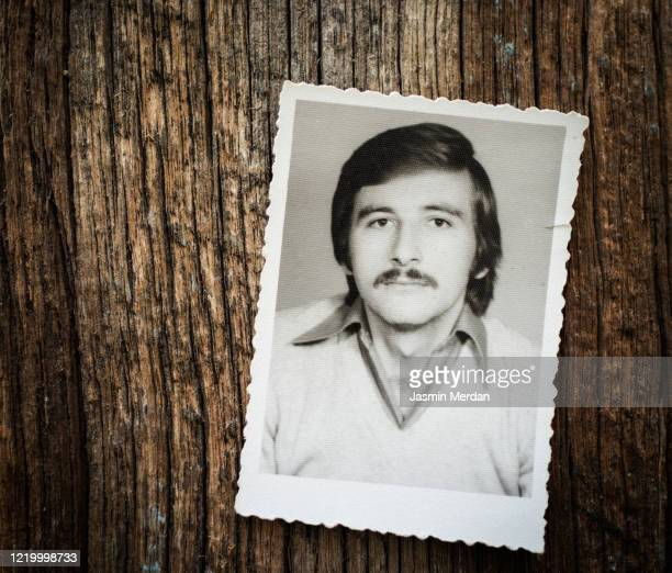 vintage framed photo of man on wooden background - foto stockfoto's en -beelden