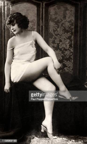 A vintage French postcard featuring a young lady in a suggestive pose in a state of deshabille published in Paris circa 1920