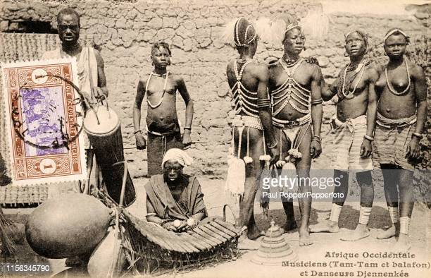 Vintage French postcard featuring members of an African musical and dancing group with a balafon and tam-tams, in Dakar, Senegal, circa 1910.