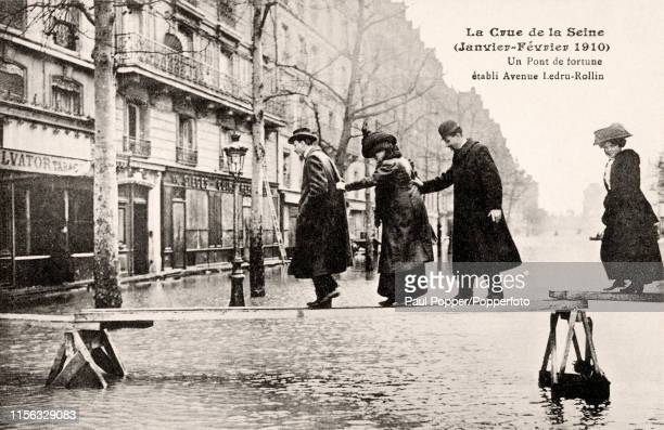Vintage French postcard featuring pedestrians carefully crossing an improvised walkway bridge above the flood waters of the Seine River at Avenue...