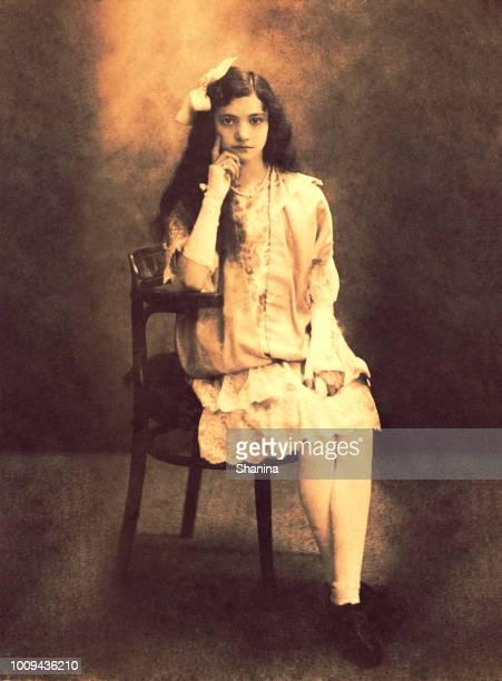 ヴィンテージの少女がカメラの前で座っています。 - 1900~1909年 ストックフォトと画像