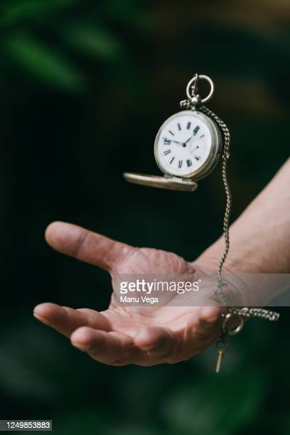 vintage golden pocket watch flying in the air on the chain in hand on green and black background. - pocket chain stock pictures, royalty-free photos & images