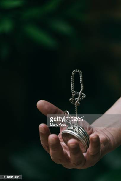vintage golden pocket watch on the chain in hand on green and black background. - pocket chain stock pictures, royalty-free photos & images