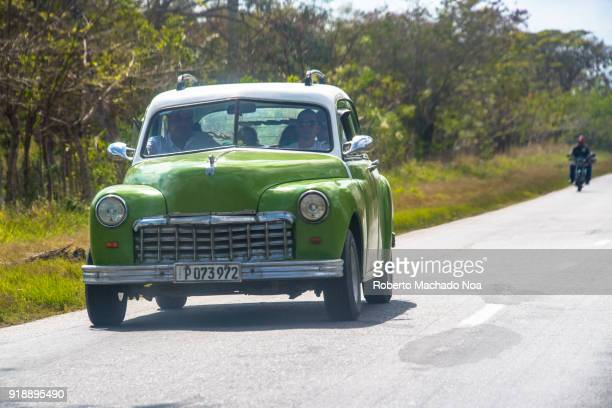 Vintage green car driving on a rural road Cuba is known for the amount of old American cars it maintains in service