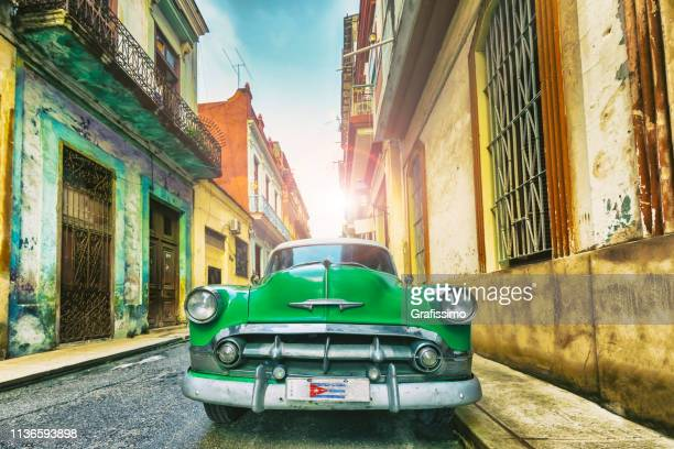 vintage green oldtimer car driving through old havana cuba - old havana stock pictures, royalty-free photos & images
