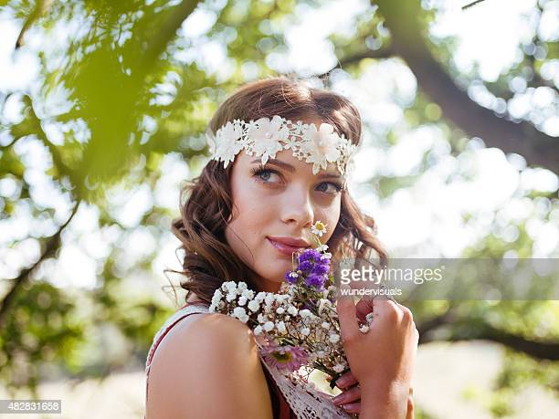 Vintage hippie girl holding flowers looking thoughtful