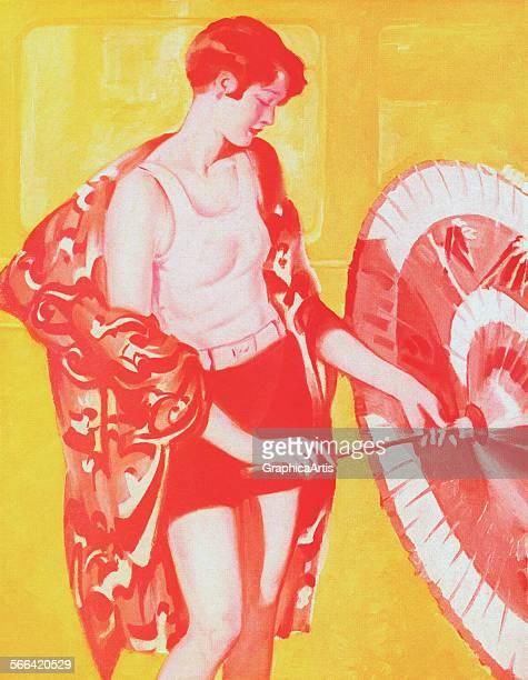 Vintage illustration of a slender flapper in a swimsuit holding a parasol engraving 1923