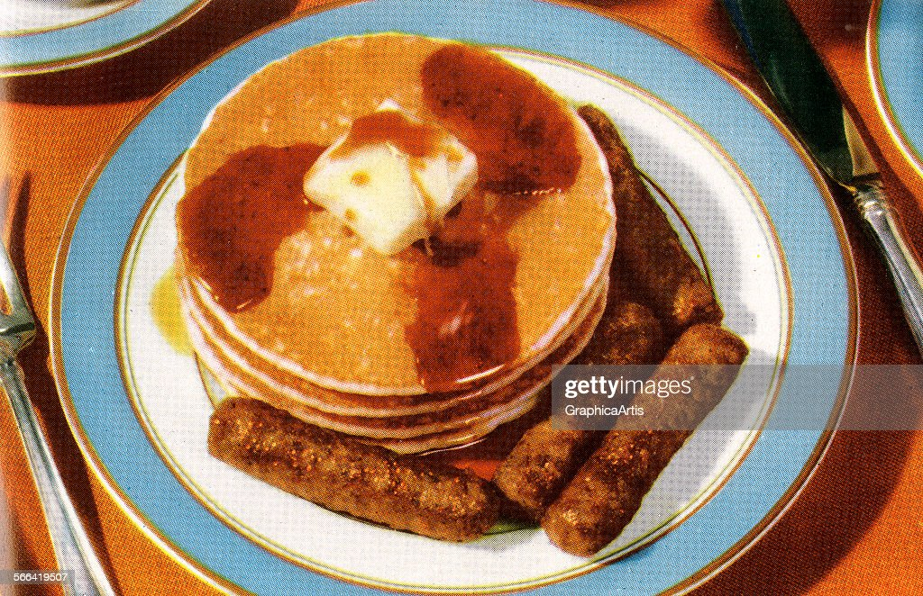 Vintage illustration of butter melting on a stack of breakfast pancakes and sausages; screen print, 1955.