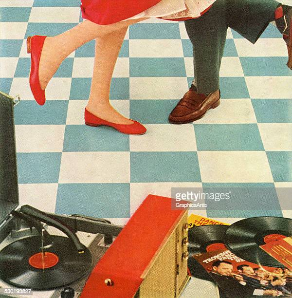 Vintage illustration of the legs of a 1950s couple dancing to music from a portable record player at a dance party 1957