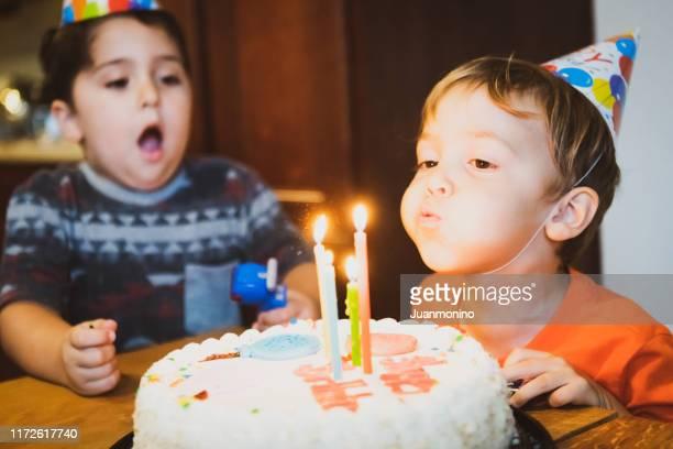 vintage afbeelding uit de jaren zeventig, kinderen blazen verjaardagstaart kaarsen - happy birthday vintage stockfoto's en -beelden