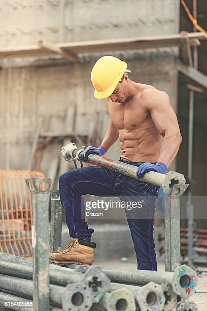 Vintage image of body builder resting on construction site