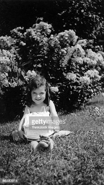Vintage image of girl with birthday cake in grass