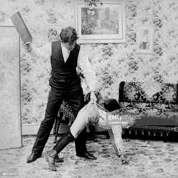 vintage image of man paddling boy - spanking stock photos and pictures