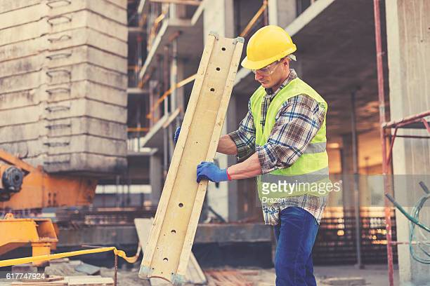 Vintage image of sweating construction worker with support planks