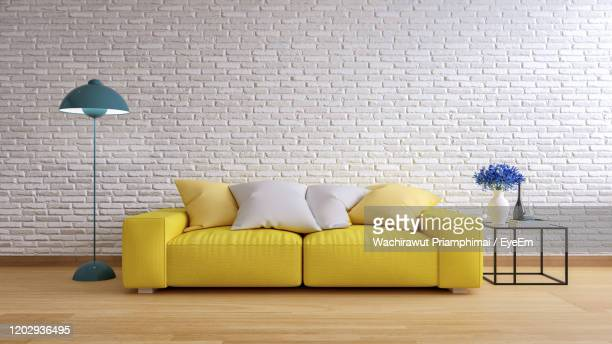 vintage interior of living room, yellow sofa with green lamp on wood flooring and white brick wall - cushion stock pictures, royalty-free photos & images