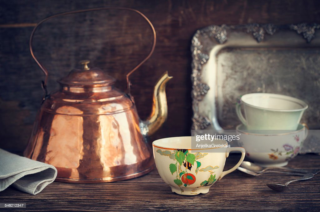 Vintage kettle and tea cups on wooden table : Stock Photo
