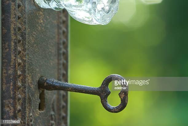 Vintage key unlocking a door outside with crystal doorknob