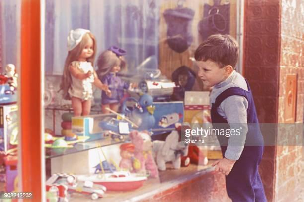 jahrgang kind betrachten einen spielzeugladen - puppe stock-fotos und bilder