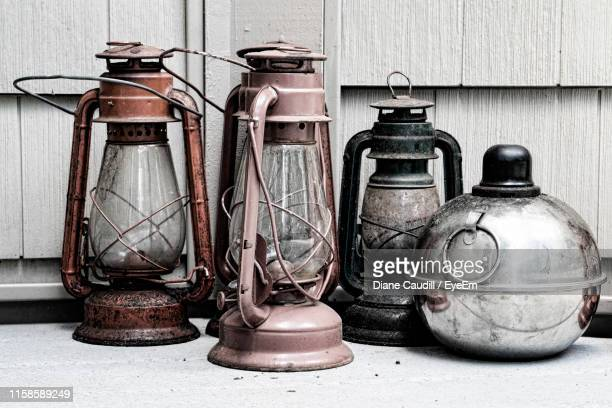vintage lanterns on table against wall - oil lamp stock pictures, royalty-free photos & images