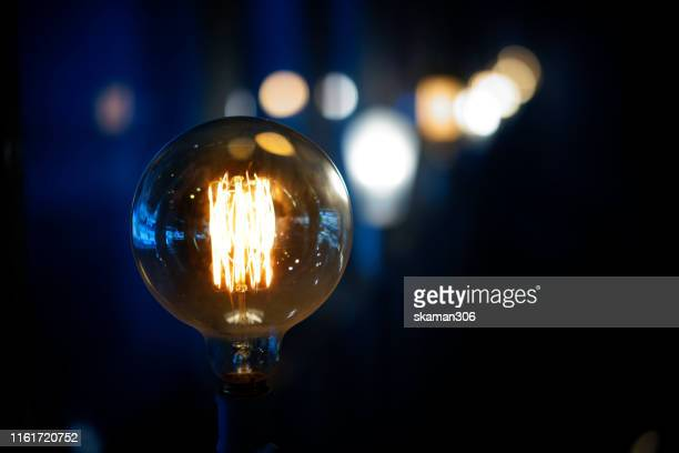 vintage light bulb with darken background - フィラメント ストックフォトと画像