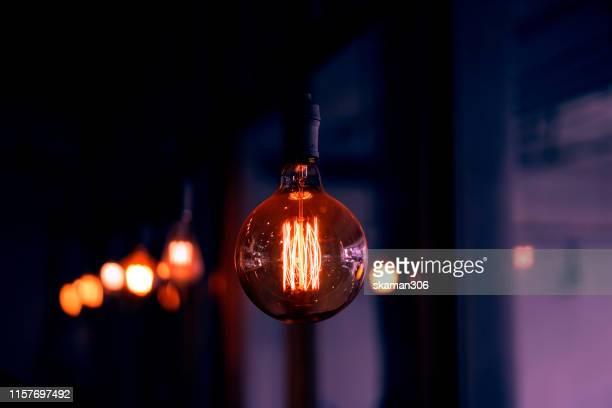 vintage light bulb with draken background - フィラメント ストックフォトと画像