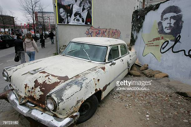 A vintage Lincoln car sits in front of grafitti featuring a portrait of Argentine revolutionary Ernesto 'Che' Guevara in a vacant lot during the 58th...