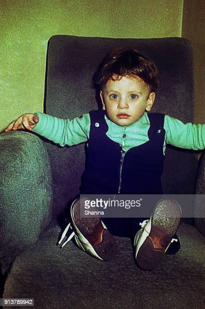 Vintage little boy on a big armchair