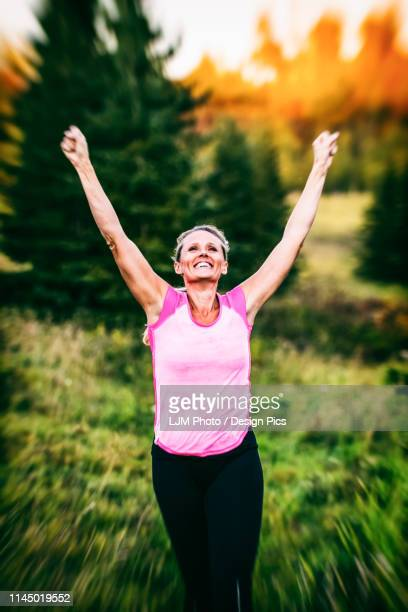 a vintage looking shot of an attractive middle-aged woman wearing active wear running with her hands in the air in a city park at sunset during a warm autumn evening - human heart beating stock pictures, royalty-free photos & images