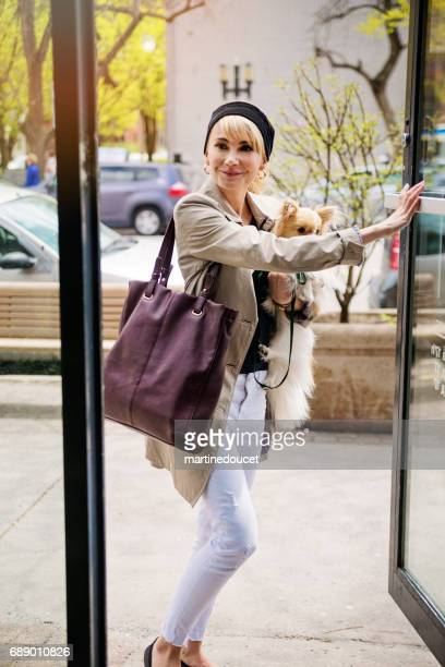 Vintage looking woman entering a store with dog in city.