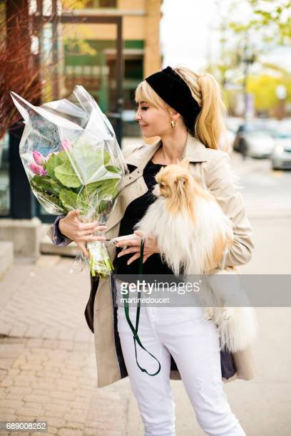 """vintage looking woman shopping with dog and flower bouquet in city. - """"martine doucet"""" or martinedoucet stock pictures, royalty-free photos & images"""