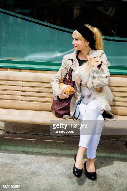 Vintage looking woman sitting on bench with dog in city.