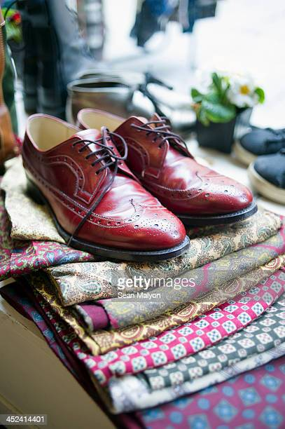 vintage men's shoes on top of pile of fabric - sean malyon stock pictures, royalty-free photos & images