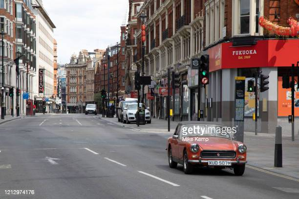 Vintage MG Midget drives along Shaftesbury Avenue on empty streets as lockdown continues and people observe the stay at home message in the capital...