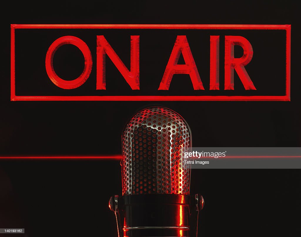 Vintage microphone and red on air neon, studio shot : Stock Photo