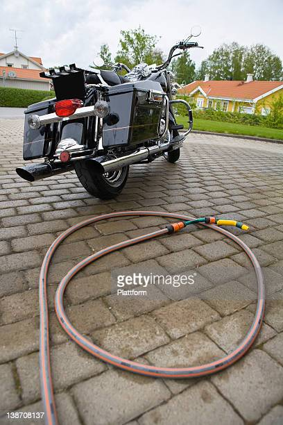 Vintage motorbike in driveway with hose on ground