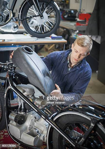 Vintage motorcycle workshop with male mechanic