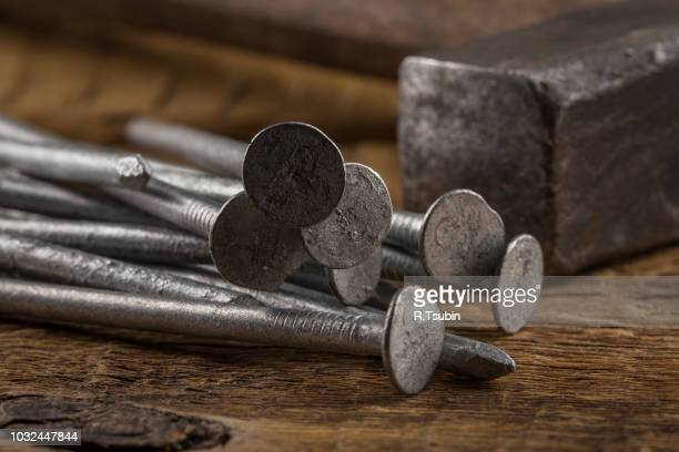 Vintage old hammer with nails on wood table background