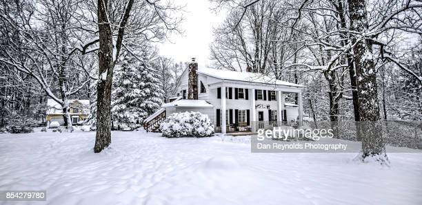 Vintage old house in fresh snow with trees