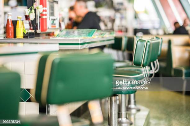 vintage padded bar stools in an american diner restaurant. - diner stock pictures, royalty-free photos & images